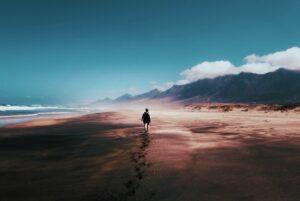 Meer. Strand. Berge. Wolken über den Bergen. Ein Mensch spaziert am Strand entlang  Foto Tom Swinnen, Pexels