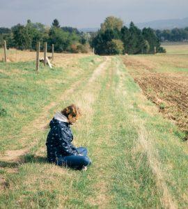 Wiese. Acker. Himmel. Eine Frau sitzt allein auf einer Wiese am Rand eines Ackers. Sie schaut nachdenklich nach unten. Nachdenklich oder traurig oder ... ?